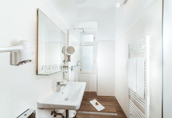 Badezimmer mit Waschbecken, Dusche und WC im Hotel Donauwalzer