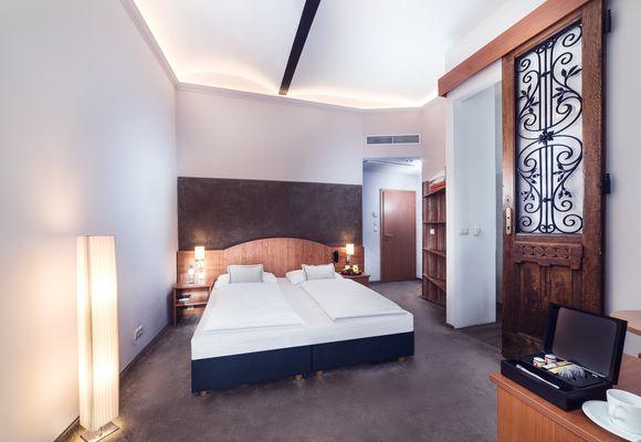 Zimmer mit Doppelbett, Schrank und Schreibtisch im Hotel Donauwalzer