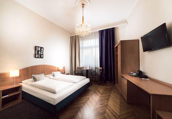Zimmer mit Doppelbett, Schrank und Schreibtisch im Boutiquehotel Donauwalzer