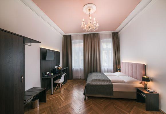 Zimmer mit Doppelbett, Schrank und Schreibtisch im Hotel